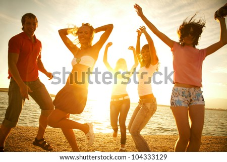 happy young teens dancing at the beach on  beautiful summer sunset - stock photo