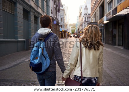 Happy young tourist couple walking street on vacation together