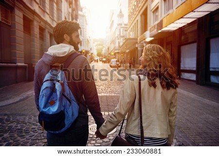Happy young tourist couple walking street on vacation together - stock photo