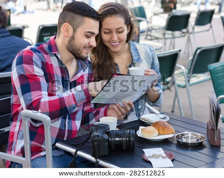 Happy young tourist couple with photocamera and map at open-air cafe. Focus on guy - stock photo