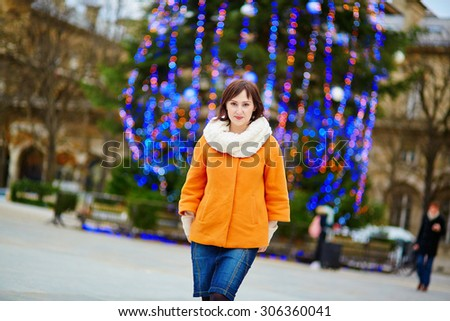 Happy young tourist in Paris on a winter day, main Parisian Christmas tree in the background - stock photo