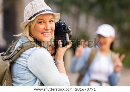 happy young tourist taking a photo of her friend with digital camera - stock photo