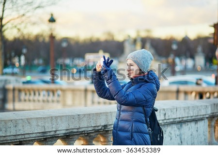 Happy young tourist taking a photo with her mobile phone in Paris, France on a winter day - stock photo