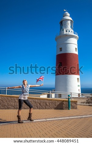 Happy young tourist woman waving a British flag. Europa Point Lighthouse on the southernmost point of Gibraltar where you can see the Strait and Africa. - stock photo