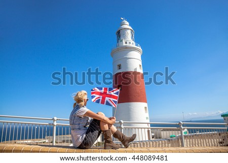 Happy young tourist woman waving a British flag in Europa Point Lighthouse, Gibraltar. - stock photo