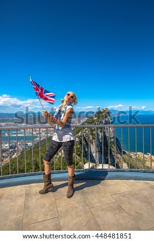 Happy young tourist woman waving a British flag on top of Gibraltar Rock. Gibraltar is a territory of South West Europe Which is part of the United Kingdom. - stock photo