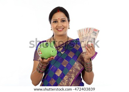 Happy young traditional woman holding Indian currency and piggy bank