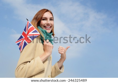 happy young travel woman holding British England flag with sky background, caucasian beauty - stock photo