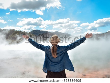 Happy young traveler woman raising hands standing in wai-o-tapu park near hot pool geyser. New Zealand - stock photo