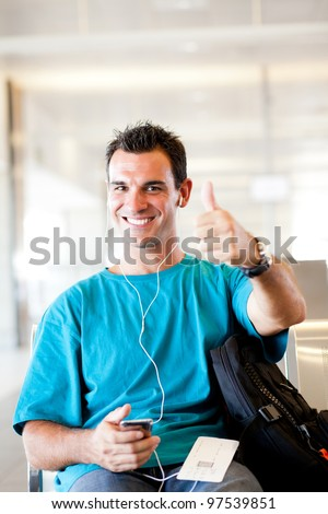 happy young traveller giving thumb up at airport - stock photo