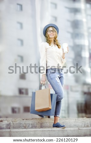 Happy young trendy woman drinking take away coffee and walking down the stairs after shopping with bags in an urban city. - stock photo