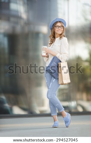 Happy young trendy woman drinking take away coffee, standing on the stairs with shopping bags, and looking aside with smile against urban city background. - stock photo