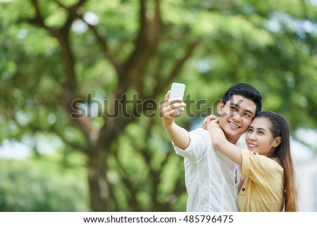 Happy young Vietnamese couple taking selfie outdoors