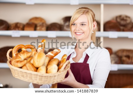 Happy young waitress giving breadbasket while looking away in cafe - stock photo