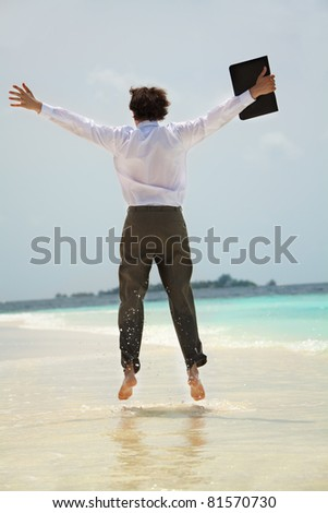 Happy young white-collar worker jumping on the shore of the sea view from behind - stock photo