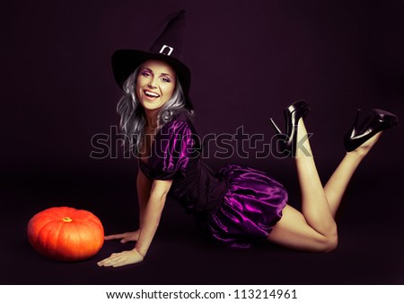 happy young witch with  a pumpkin, against dark studio background - stock photo