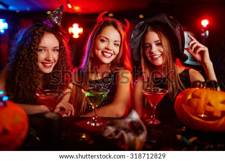 Happy young witches drinking cocktails at bar counter