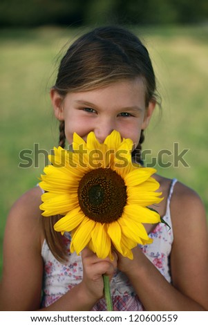 Happy young with a sunflower on a meadow - stock photo