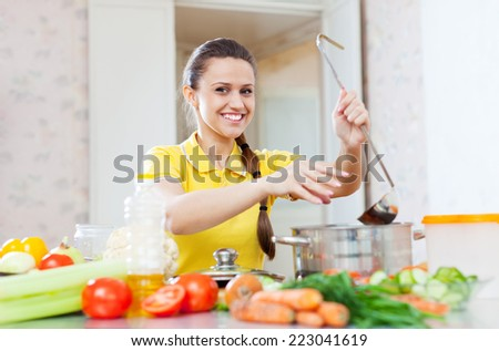 Happy young woman adds spice or salt in saucepan at domestic kitchen - stock photo