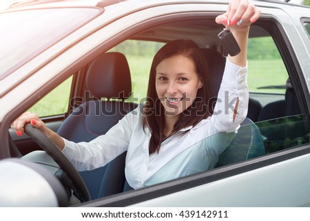 Happy young woman after car purchase. - stock photo