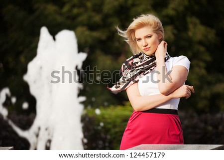 Happy young woman against a city fountain