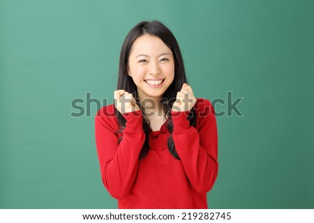 happy young woman against green background - stock photo