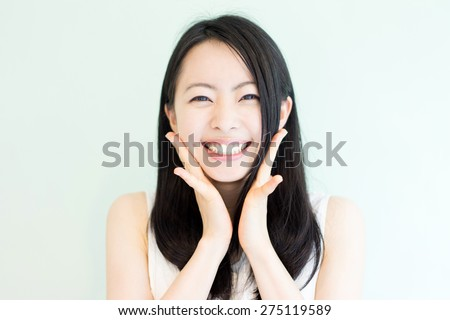 happy young woman against light green background - stock photo