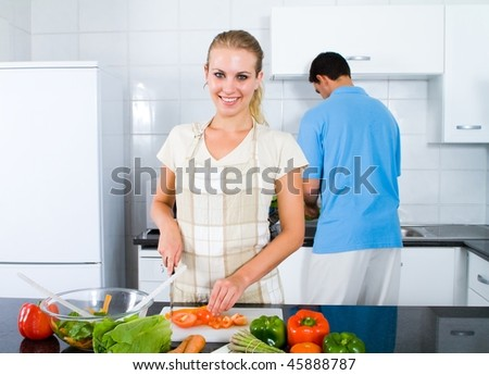 happy young woman and boyfriend cooking food in kitchen