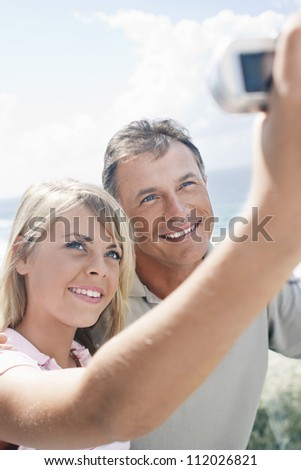 Happy young woman and father taking self-portrait