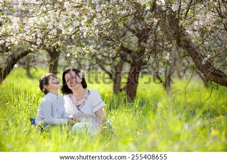 Happy young woman and her child talking and having rest in spring apple garden - stock photo