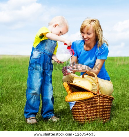 happy young  woman and her son having a picnic outdoor on a summer day - stock photo