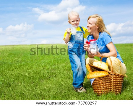 happy young  woman and her son having a picnic outdoor on a summer day