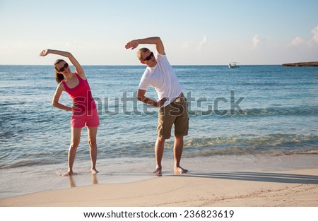 Happy young woman and man doing exercises on the sea coast at dawn