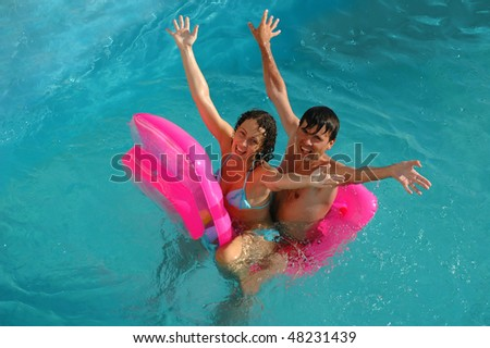 Happy young woman and the man sit on a mattress in pool - stock photo