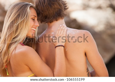 Happy young woman applying cream on boyfriend's back