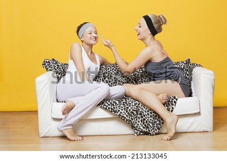 Happy young woman applying face pack on friend's face while sitting on sofa against yellow wall - stock photo