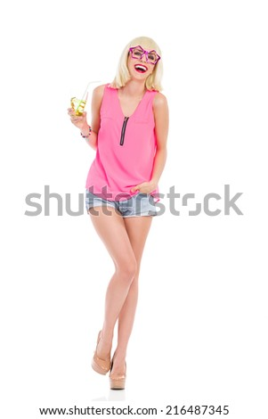 Happy young woman at the party. Smiling blonde young woman with star shaped glasses standing on one leg and holding a drink. Full length studio shot isolated on white. - stock photo