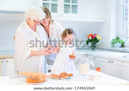 Happy young woman baking a cake with her senior mother and cute toddler girl n a beautiful white kitchen - stock photo