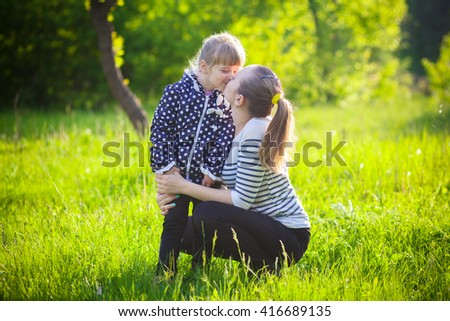 Happy young woman being kissed by a cute little girl - stock photo
