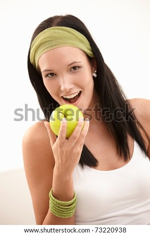 Happy young woman biting green apple, smiling, isolated on white.? - stock photo