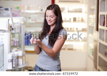 Happy young woman buying a perfume. Shallow DOF. - stock photo