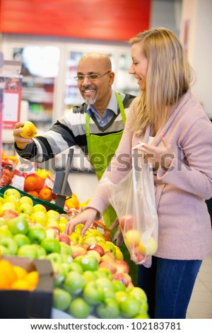 Happy young woman buying fruits with shop assistant in the background