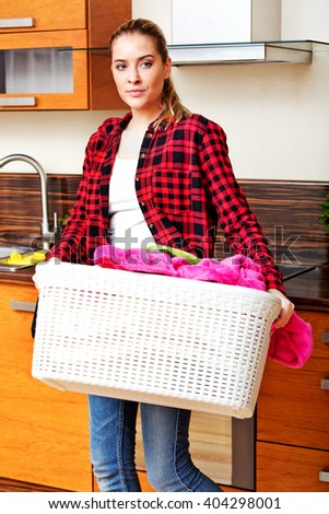 Happy young woman carrying laundry basket in kitchen - stock photo
