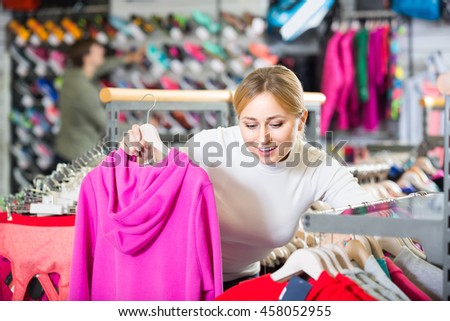 Happy young woman choosing a cardigan in the sport clothes shop