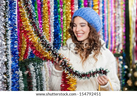 Happy young woman choosing tinsels at Christmas store - stock photo