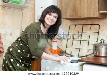 Happy young woman cleans gas stove with melamine sponge in kitchen