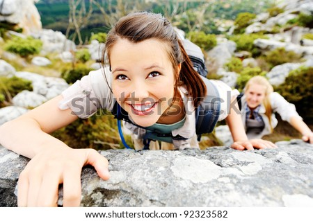 happy young woman climbs up a rock face while exploring the wilderness - stock photo