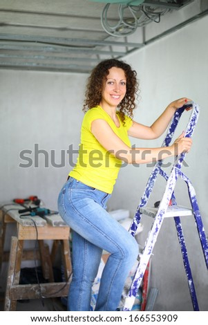 Happy young woman coming down the ladder in the room