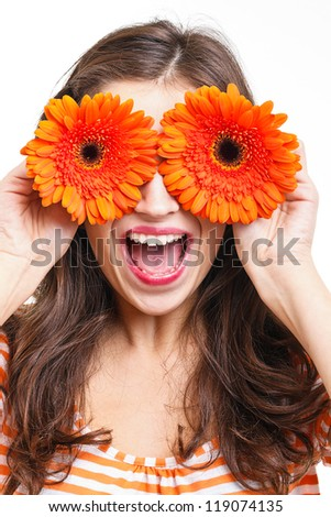 Happy young woman covering her eyes with flowers - stock photo