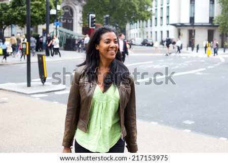 happy young woman crossing the road.  - stock photo